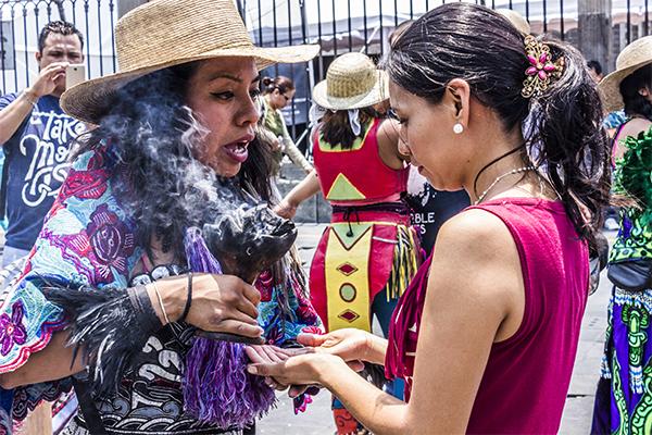 """Mientras los 'Danzantes' ejecutan los rituales, los turistas los observan con curiosidad y reciben rituales de """"limpias"""" a cambio de donaciones o aportes económicos."""